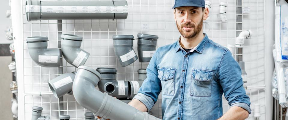 mężczyzna trzymający plastikową rurę